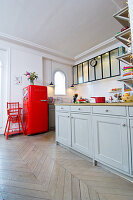 Grey base units and red fridge in period apartment