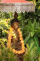 Buddha statue decorated with garland of flowers below Balinese parasol