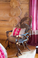 Quaint armchair made from antlers and embroidered cushion in log cabin