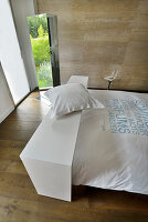 Table over bed in bedroom with wooden floor and stone wall