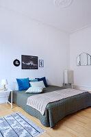 Doppelbett mit Tagesdecke und Kissen in schlichtem Schlafzimmer