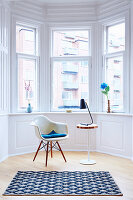 Classic chair, side table, reading lamp and rug in window bay