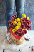 Young woman wearing jeans with fresh cut flowers in a straw bag