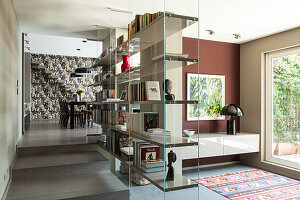 Glass partition shelves in open-plan interior with dining area and staircase in background against patterned wallpaper
