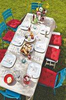 Gedeckter Tisch mit Papiertischdecke und Menükarte im Garten