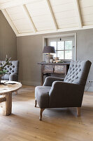 Classic armchair in living room with grey wall and wooden floor
