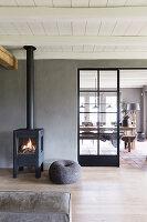 Brennendes Feuer im Schwedenofen vor grauer Wand zum Esszimmer