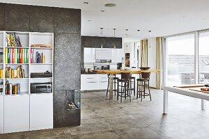 Weisses Einbauregal umgeben von beschichteter Wand und Gaskamin, Blick in offene Küche