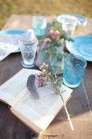 Aufgeschlagenes Buch auf dem gedeckten Tisch im Freien