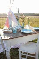 Romantisch gedeckter Tisch auf der Wiese vor einem Tipi