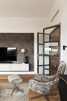 Sessel mit passendem Fusshocker in elegantem Wohnhzimmer, offene Glastür, Fernseher auf Hängeschrank