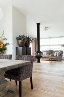 Rustikaler Holztisch mit eleganten Polsterstühlen, im Hintergrund Kamin und Lounge