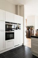 Elegante, weiße Küche mit Einbaugeräten