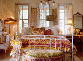 Lavish textiles on old metal bed in romantic bedroom