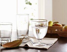 Wassergläser auf dem Tisch mit gestreifter Serviette und Obst