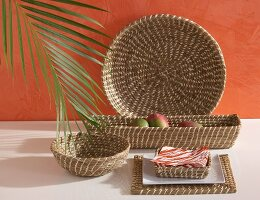 Set of seagrass baskets of different shapes against orange wall