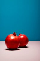 Two red pomegranates against blue background