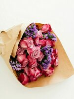 Bouquet of roses and sea lavender wrapped in brown paper