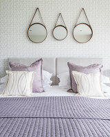 Three round mirrors hung above bed with purple scatter cushions