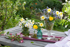 Small bouquets in glasses on coasters with bark and snail shells