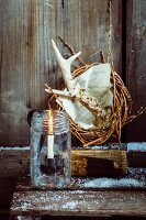 Rustic Christmas arrangement of willow wreath, antlers and candle