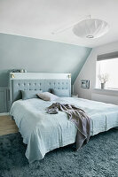 Blue and white bedroom with sloping ceiling