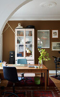 Desk in study with brown wall and white stucco ceiling
