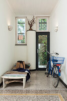Blue bicycle and sun lounger in foyer with terrazzo floor