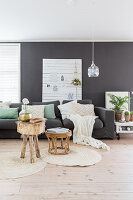 Sofa in front of white panel on black wall in Bohemian-style living room