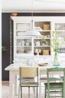 Various chairs around dining table in front of glass-fronted cabinet