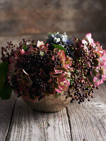 Elderberries and hydrangea flowers in vase on wooden table