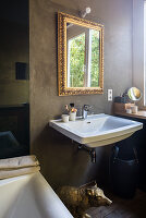 Sink below gilt-framed mirror on bathroom wall