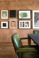 Green retro armchair at table in front of gallery on pictures on marbled wall