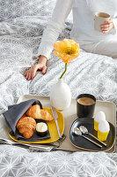 Frühstückstablett mit Croissant, Eiern, Kaffee und gelber Mohnblüte auf dem Bett, Frau im Hintergrund