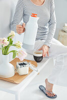 Woman with thermos flask of coffee, yoghurt with blueberries and vase of tulips on tray