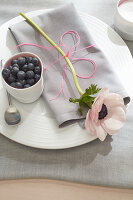 Anemone and bowl of blueberries on place setting