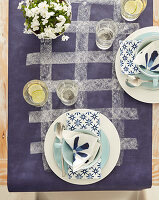 Place settings with white and blue serviettes on purple tablecloth