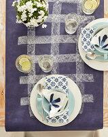 Gedeck mit weiß-blauen Servietten auf lila Tischdecke