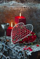 Red roses in wire love heart in front of red pillar candles