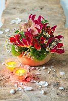 Red arrangement of flame lily, orchids and Indian mallow