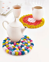 A homemade pot holder made from colourful felt balls and crocheted dots