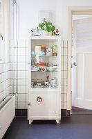 Vintage Vitrinenschrank mit Geschirr vor gefliester Wand