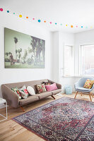 Scatter cushions on retro sofa below large photo on living room wall