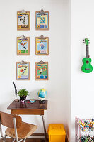 Vintage desk and chair below picture cards on clipboards and ukulele on wall