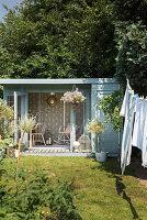 Wäscheleine mit aufgehängter Wäsche im Garten, im Hintergrund Gartenhäuschen