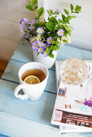 Eine Tasse Tee, Blumen und Glaskugel auf Buch