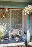 Alter Schaukelstuhl aus Holz im Gartenhäuschen mit tapezierter Wand