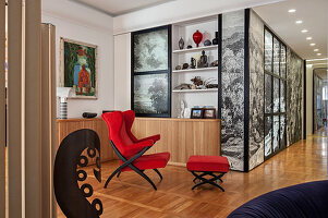 Red designer armchair with footstool in open-plan interior