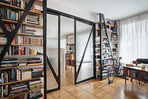 Floor-to-ceiling bookshelves, glass sliding doors and bicycle in front of window in study