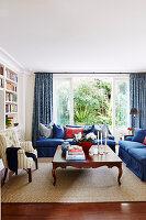 Blaue Polstergarnitur, antiker Couchtisch und Sessel im Wohnzimmer